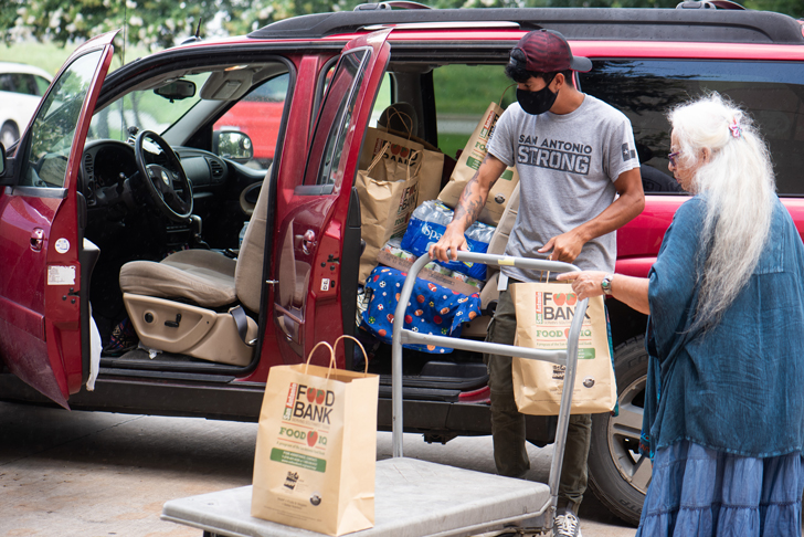 Emma and a Food Bank volunteer loading bags of food into a car.