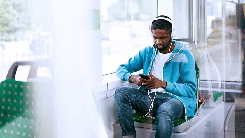man writing music listening to headphones